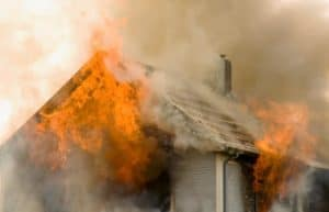 Flames shoot out of an upper story and engulf the roof of a house on fire.